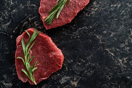 top view of uncooked beef sirloins with rosemary on black marble background