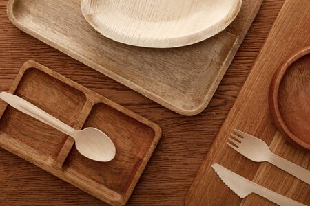 top view of wooden dish and cutting board with plates and cutlery on brown background