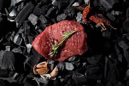 top view of raw beef steak with rosemary, salt and pepper near garlic cloves and dried cayenne on charcoals Banco de Imagens