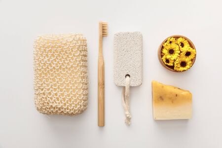 flat lay with bath sponge near toothbrush, piece of soap, pumice stone and cup with flowers on white background Archivio Fotografico