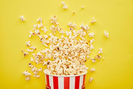 top view of delicious popcorn scattered from striped bucket on yellow background 스톡 콘텐츠