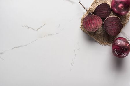 top view of red onions and beetroot halves on marble surface with hessian