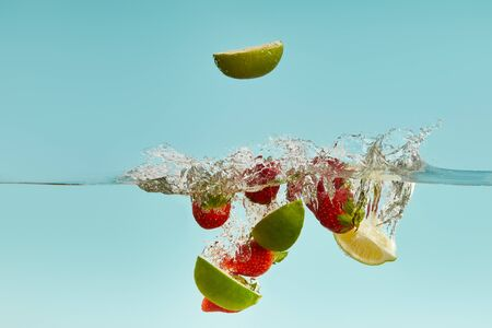 ripe lime pieces and strawberries falling deep in water with splash on blue background