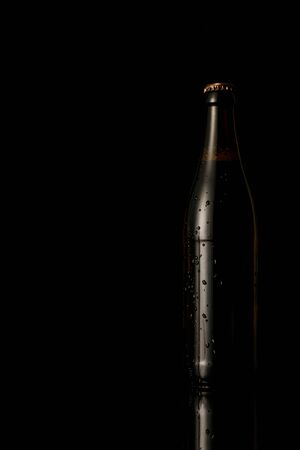 glass bottle of beer with water drops isolated on black