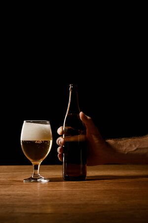 partial view of man holding bottle near glass with beer and foam on wooden table isolated on black