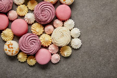 Top view of meringues, macaroons and fluffy white and pink zephyr on gray background