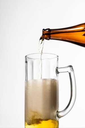 beer pouring from bottle into glass with foam isolated on white