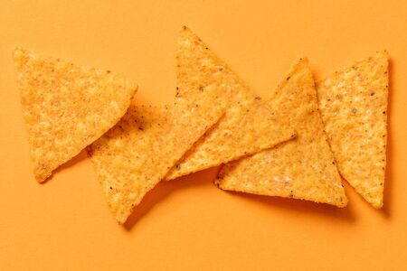 top view of delicious traditional crunchy Mexican nachos on orange background