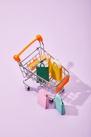 few small paper bags near toy cart with colorful shopping bags on violet background