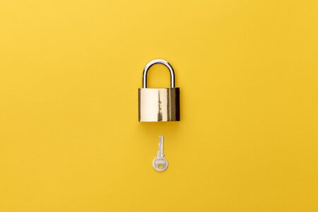 top view of padlock and key on yellow background Standard-Bild