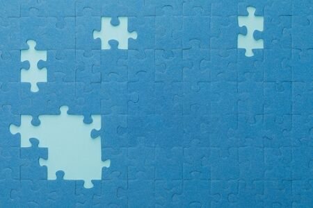 top view of unfinished blue jigsaw puzzle on lighter background