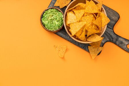top view of crispy Mexican nachos served with guacamole on wooden cutting board on orange background