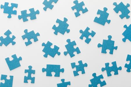 top view of scattered blue jigsaw puzzle on white background