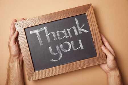 partial view of man holding chalkboard with thank you lettering Stock Photo