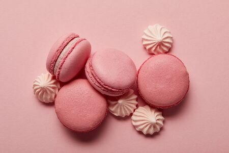 Pink macaroons with pink meringues on pink background