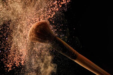 soft cosmetic brush with colorful orange powder explosion on black background