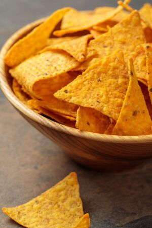 close up view of Mexican nachos in wooden bowl on stone table Stock Photo