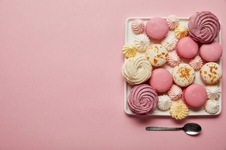 Flat lay with assorted meringues and macaroons on square dish with spoon on pink background