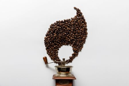 top view of vintage coffee grinder near flame made of coffee grains on white background