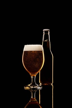 bottle and glass of beer with white foam isolated on black Stock Photo