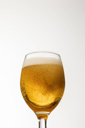 low angle view of glass of beer with foam isolated on white