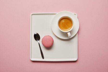 Top view of pink macaroon with spoon and cup of coffee on big square white dish on pink background