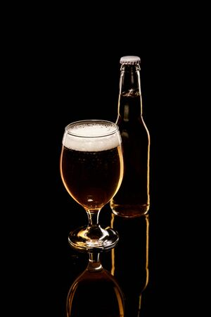 bottle and glass of beer with white foam and bubbles isolated on black