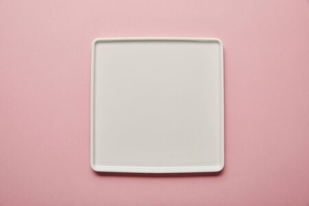 Top view of white square flat plate on pink background