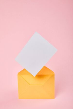 yellow envelope with blank white card on pink background
