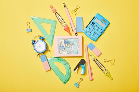 top view of school supplies scattered near box with clips on yellow background