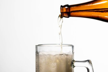 beer pouring from bottle into glass with white foam isolated on white