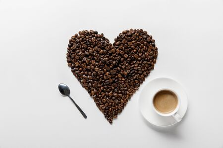 top view of coffee in cup on saucer with heart made of coffee grains and spoon on white background 写真素材