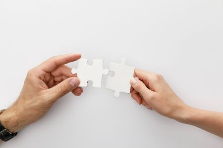 cropped view of woman and man holding pieces of jigsaw puzzle on white background