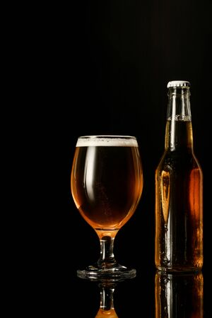 glass of beer with foam near bottle isolated on black Stock Photo