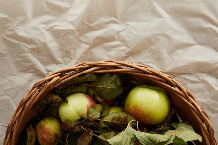 top view of basket with apples on parchment paper with copy space