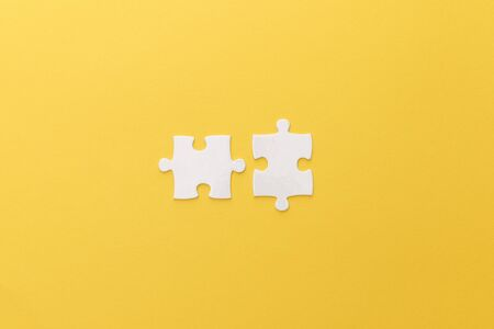 top view of white puzzle pieces on yellow background