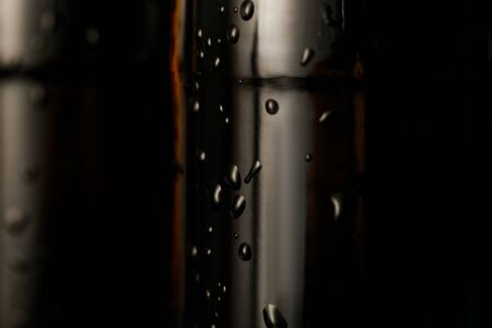 close up view of glass bottle of beer with water drops isolated on black