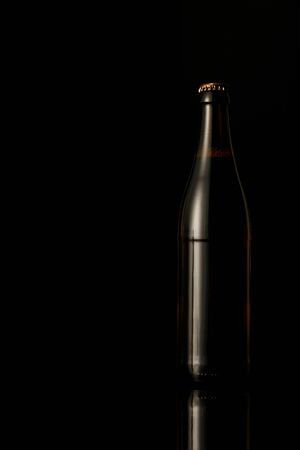 dark glass bottle of beer isolated on black