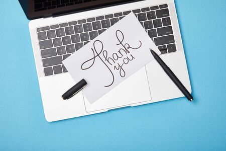 top view of laptop and card with thank you lettering and pen on blue background Stock Photo