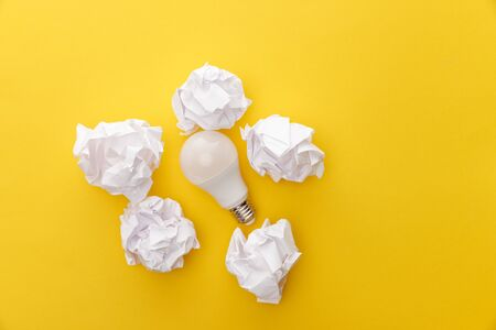 top view of light bulb between crumpled paper on yellow background Stock fotó