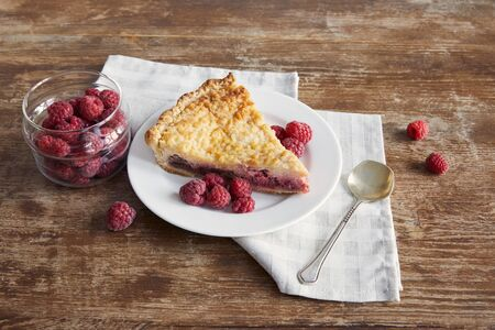 piece of tasty pie with raspberries on plate near teaspoon and napkin on wooden table