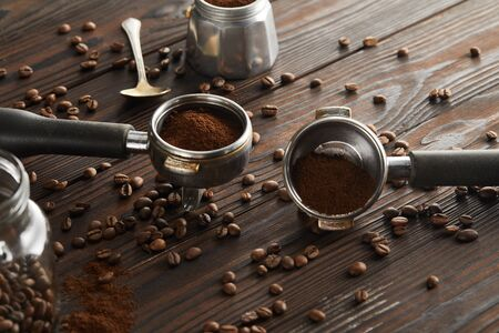 Portafilters near spoon, glass jar and geyser coffee maker on dark wooden surface 스톡 콘텐츠
