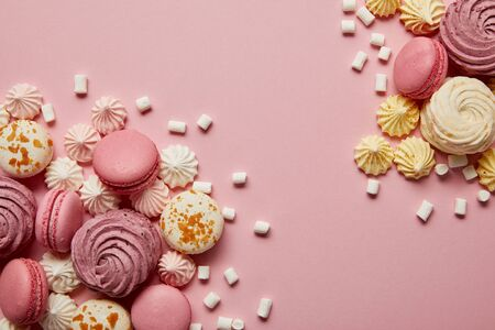 Smashed delicious sweet meringues, macaroons and small marshmallows pieces on pink background 写真素材