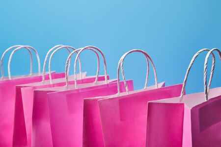 few pink paper shopping bags on blue background