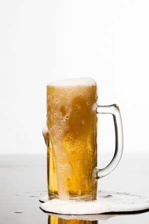 wet glass of beer with foam and puddle on surface isolated on white Stockfoto