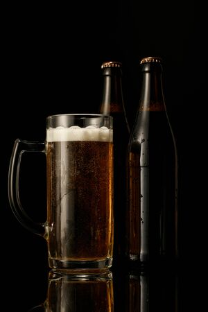 glass of beer with foam near wet bottles isolated on black Stock Photo