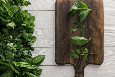 Top view of brown wooden cutting board with parsley, basil, cilantro and peppermint leaves near bundles of greenery on white surface