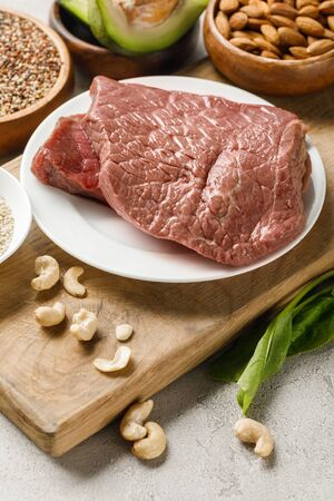 raw meat on wooden chopping board with nuts, ketogenic diet menu