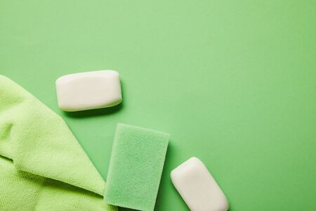 top view of white soaps, rag and sponge on green background