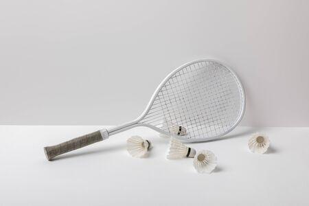 white badminton shuttlecocks near white racket on white background
